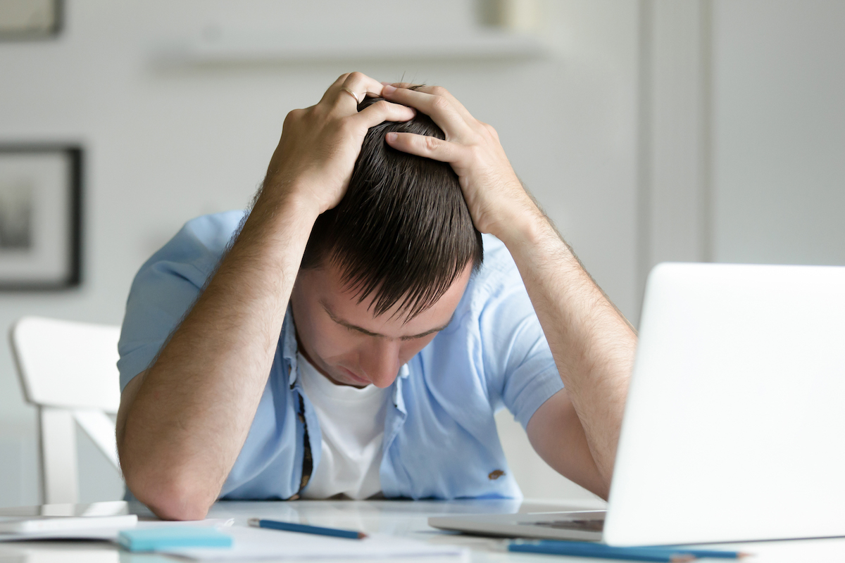 Man holding his head in despair by a laptop computer
