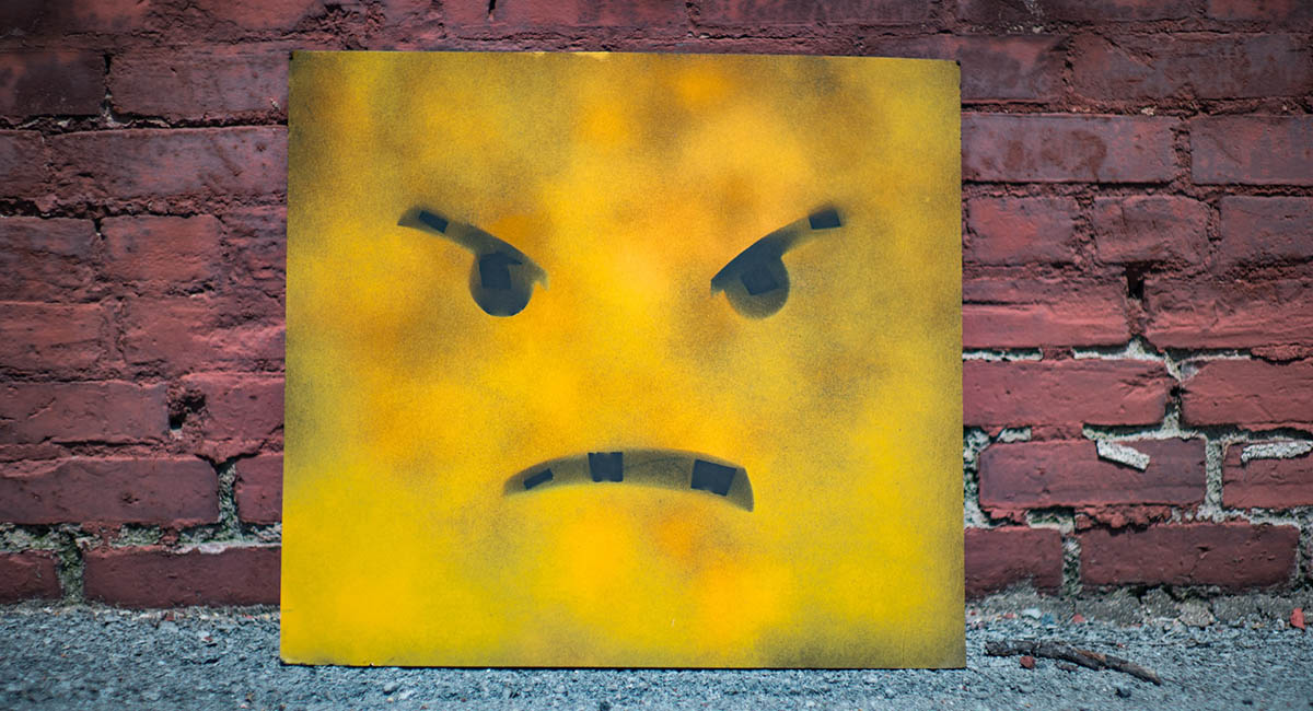 Yellow square with angry face leaning against a brick wall