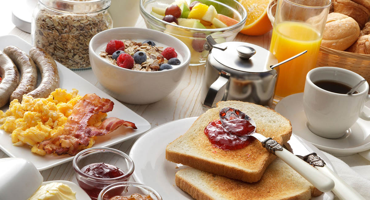 Toast, eggs, bacon, cereal, juice, fruit, sausages, and coffee on a table