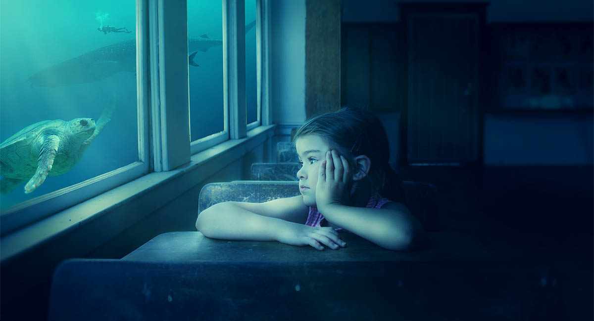 Young girl in classroom looking out the window at undersea scene with turtle