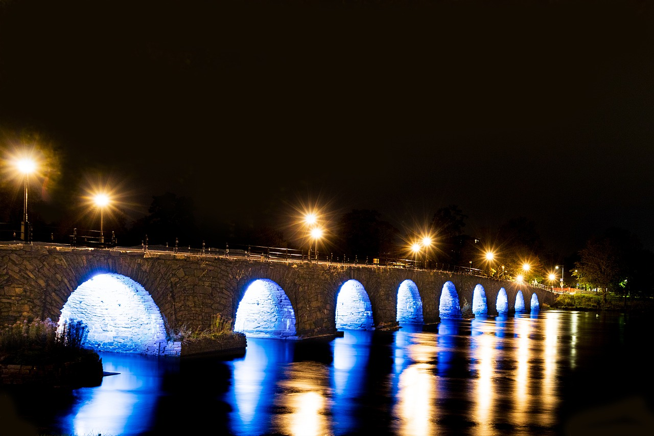 Long stone bridge over water at night