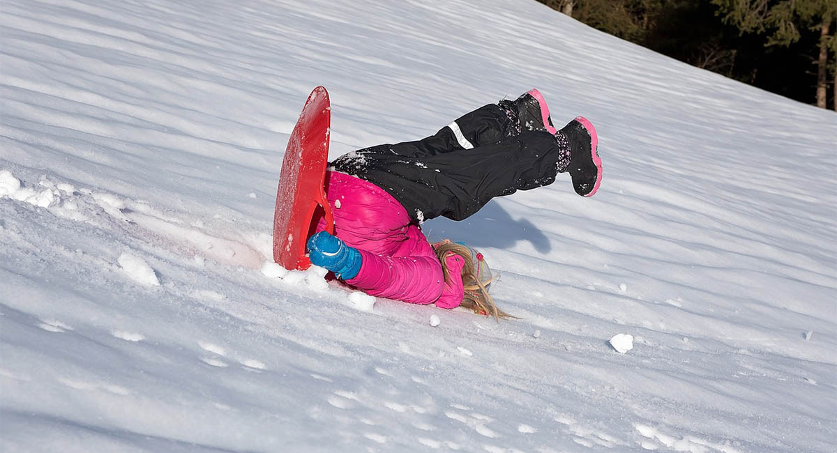 Child falling off a toboggan and sliding downhill backwards on her head