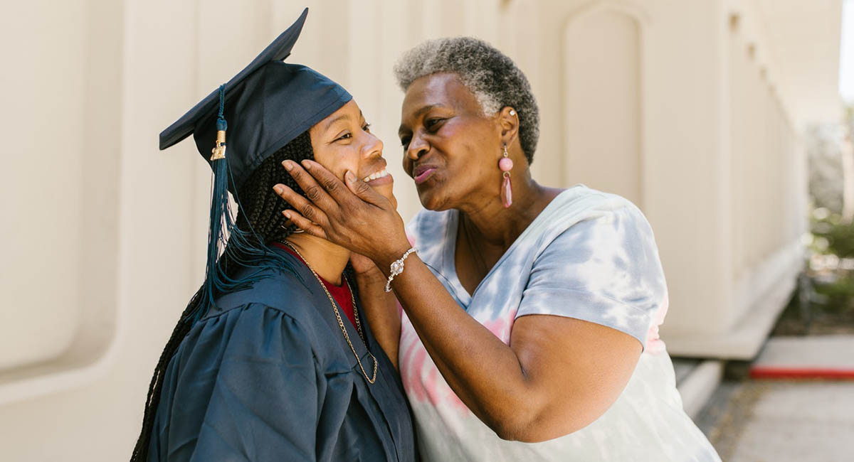 Woman graduate in cap and gown being kissed by her mother
