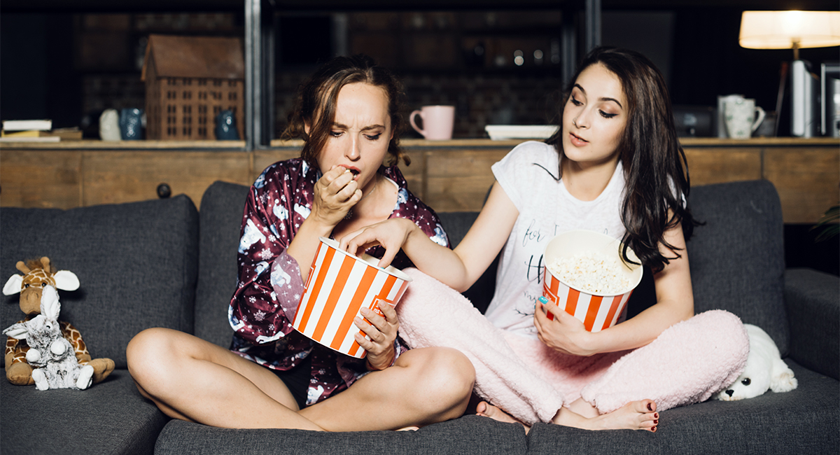 Two young women eating popcorn with one of them grabbing popcorn out of the other's bucket