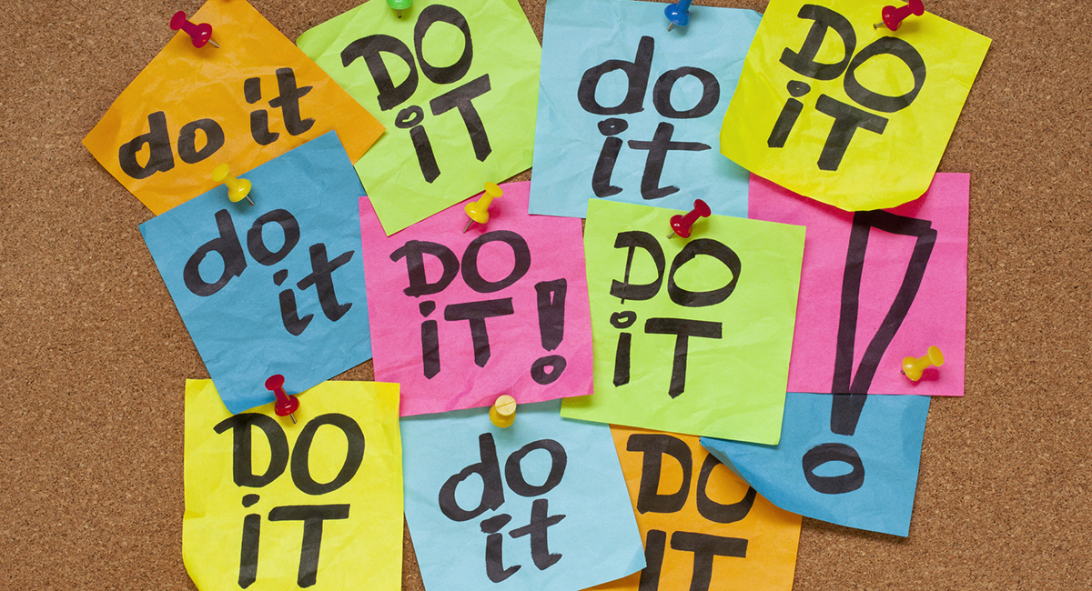 """Multicolored post-its with the words """"Do it"""" on a bulletin board"""