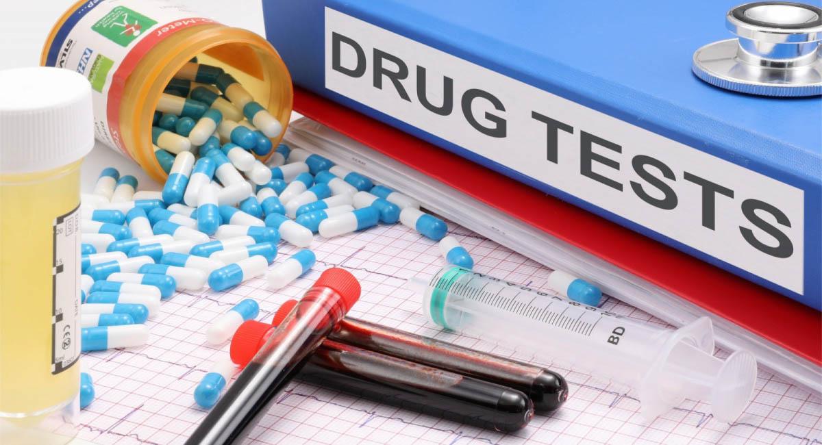 """Drugs, test tubes, syringe, notebook with label """"DRUG TESTS"""""""
