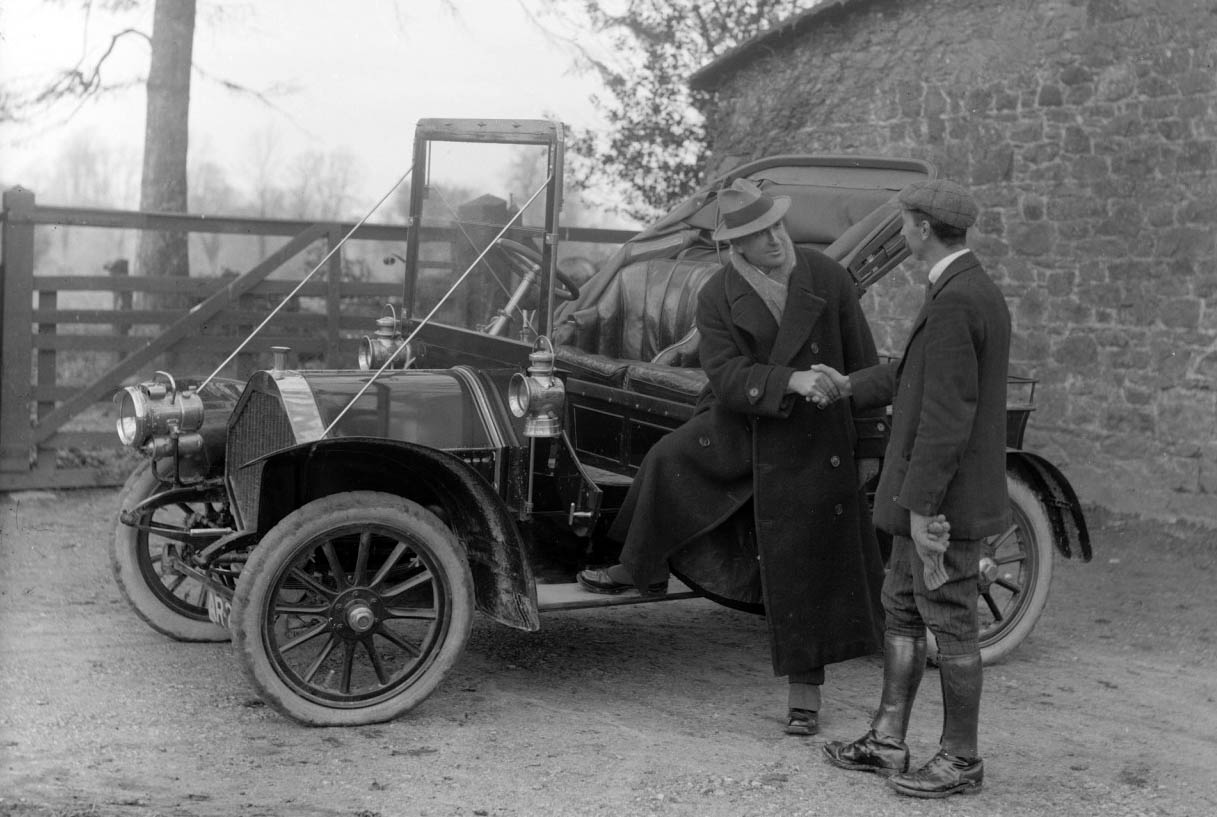 Two men shaking hands by early automobile (1900s)