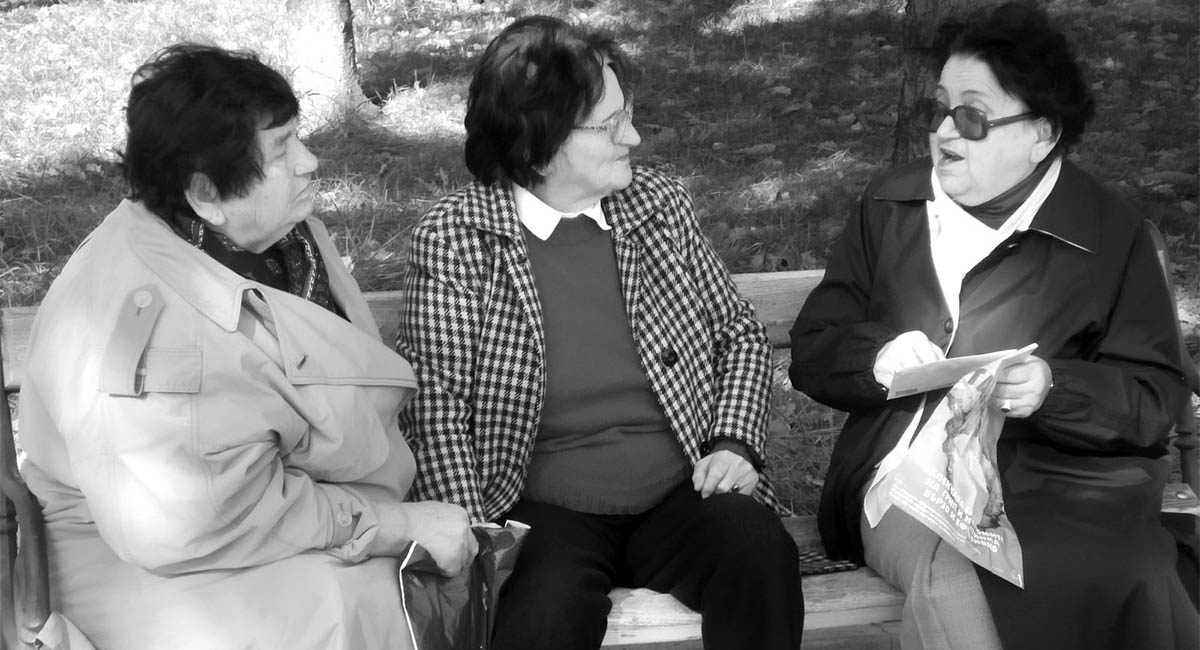 Three older women seated on a park bench, talking