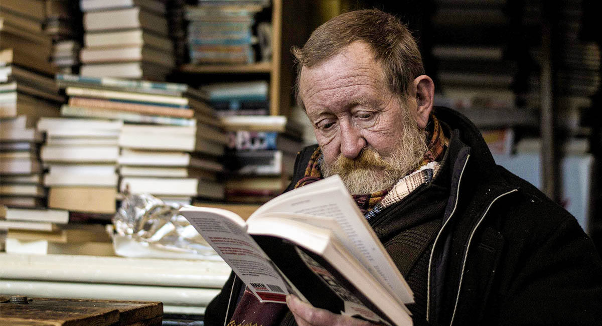 Older man reading a book with stacks of books in the background