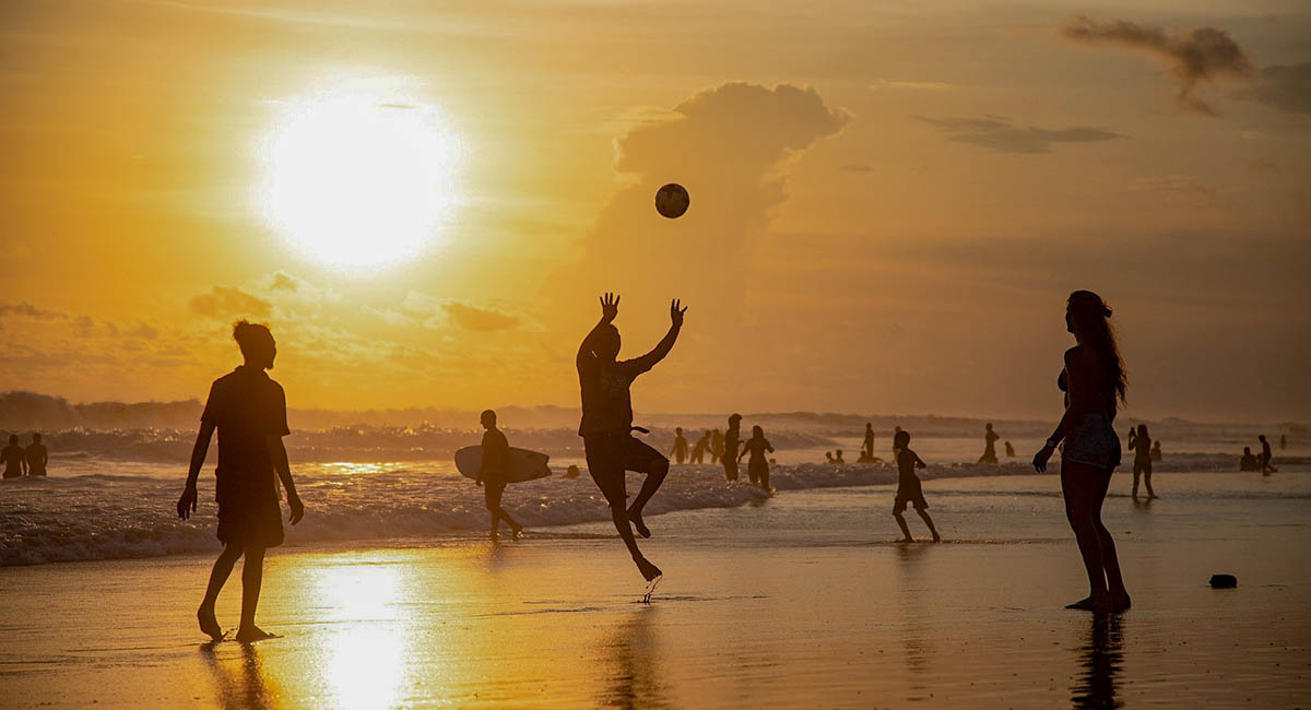 Silhouettes of people playing beach volleyball at sunset