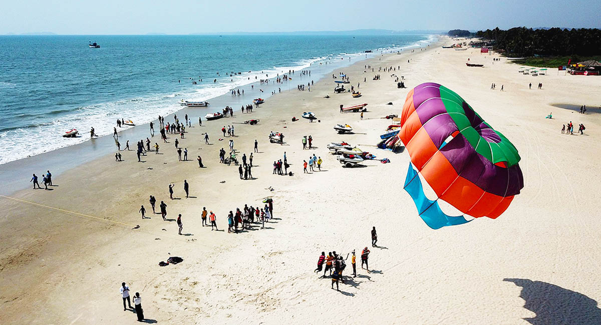 birds-eye view of people on a beach with large kite in the foreground