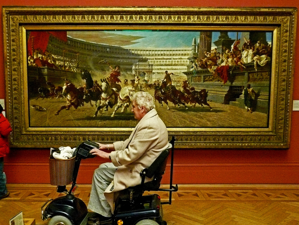Older woman in a wheelchair in front of large artwork