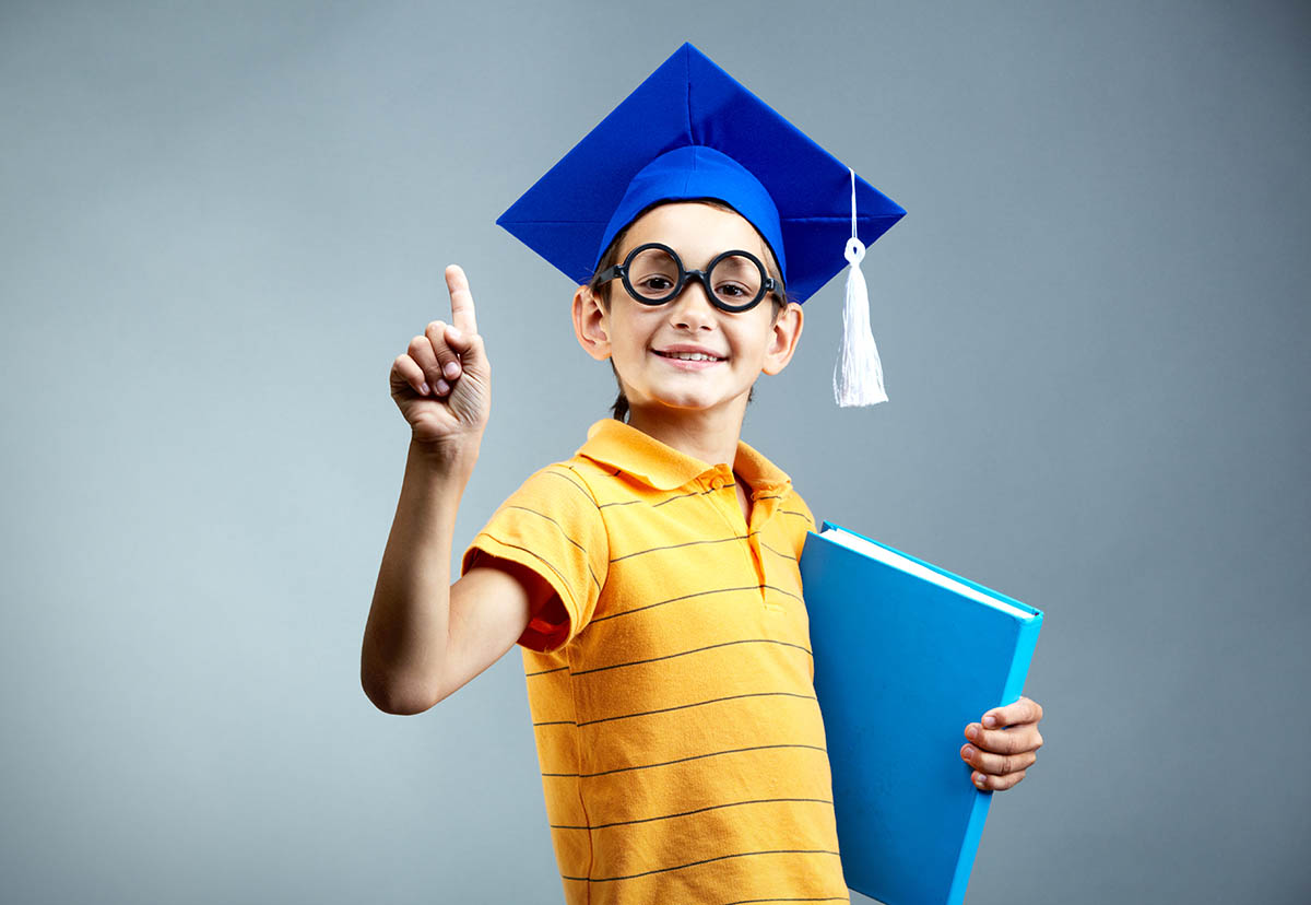 Young boy in graduation cap with binder under his arm