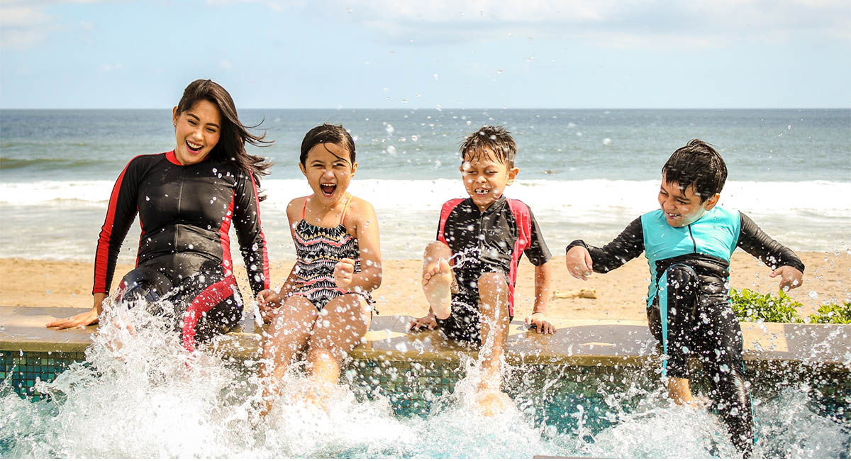 Group of children sitting on the edge of a pool by a beach splashing with their feet