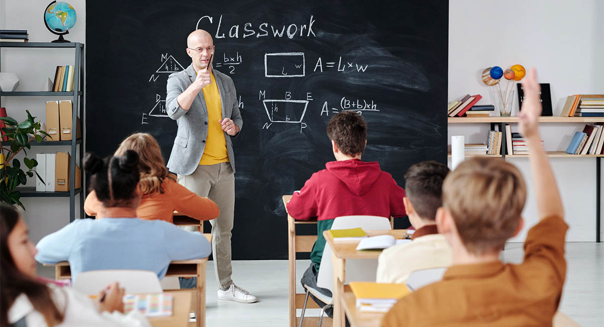 High school classroom with teacher at blackboard and student raising his hand