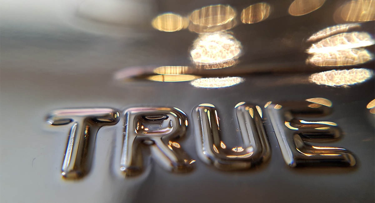 "The word ""true"" in embellished letters on gold"