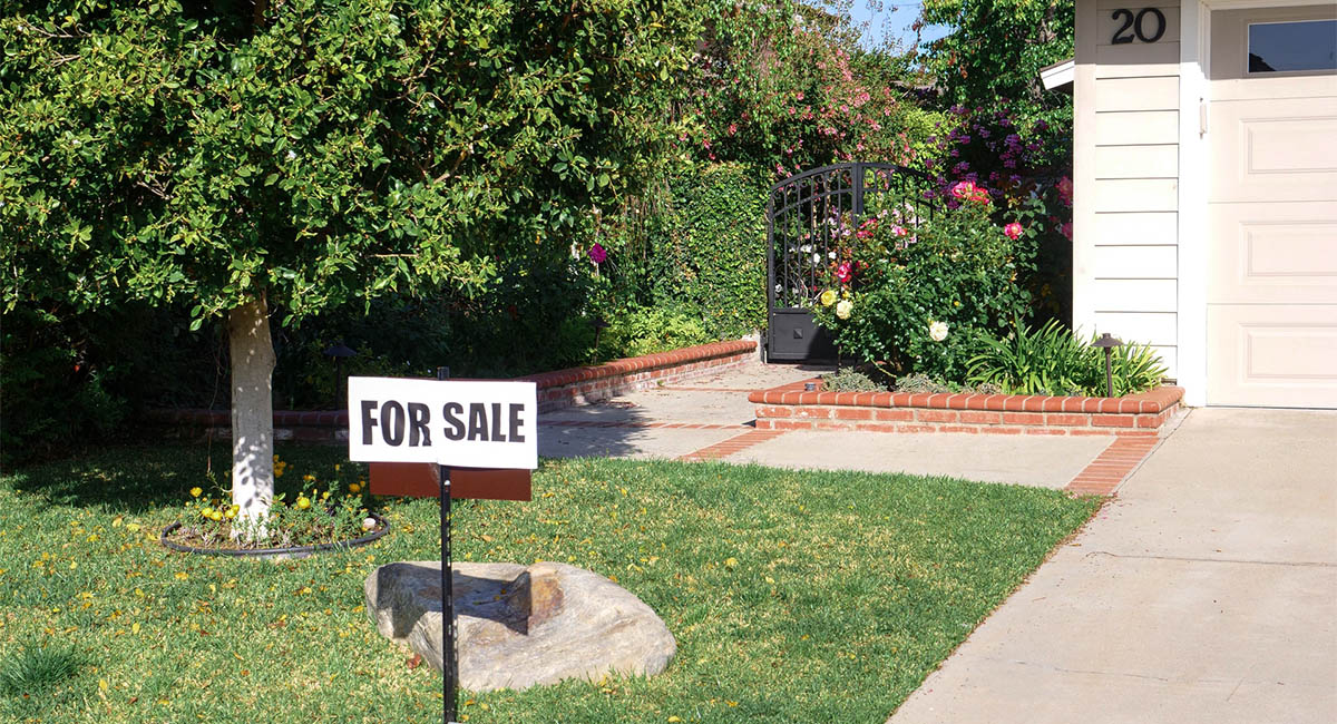 FOR SALE sign in front of corner of house with garden