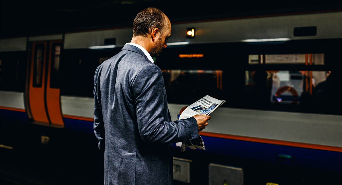 Businessman reading a newspaper while waiting for a subway train