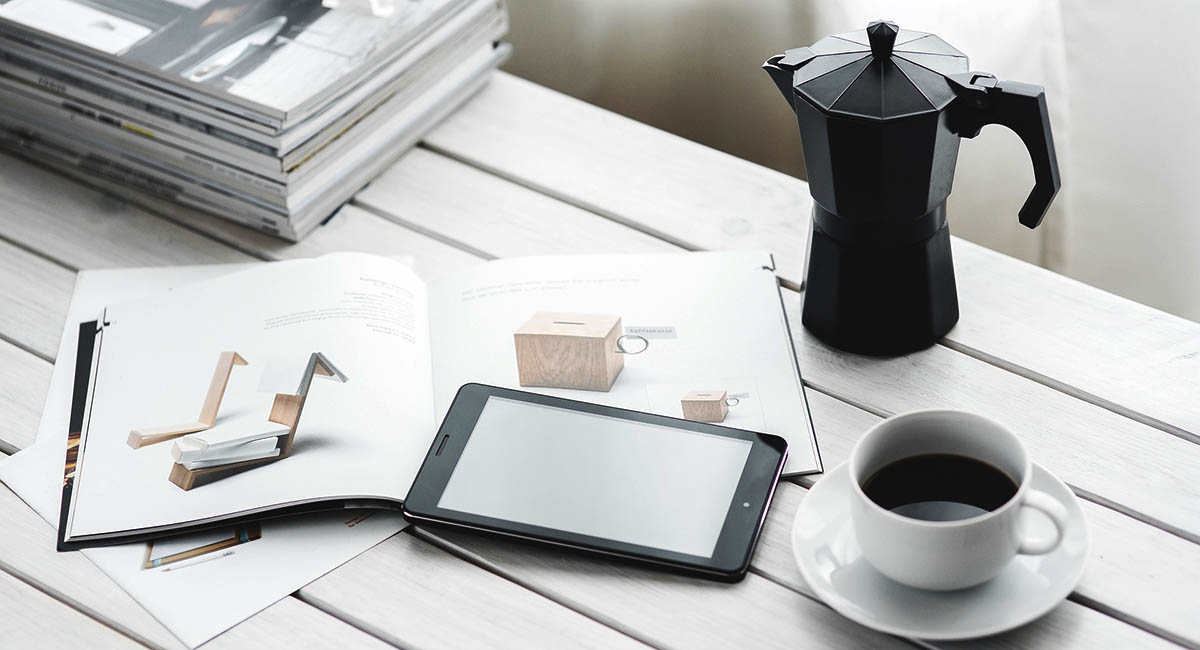 Magazines, cellphone, coffee pot and mug on white table