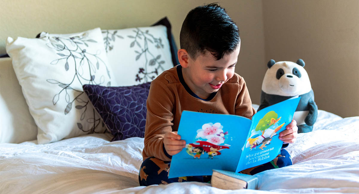 Young boy reading a book on his bed, with a plush toy panda bear