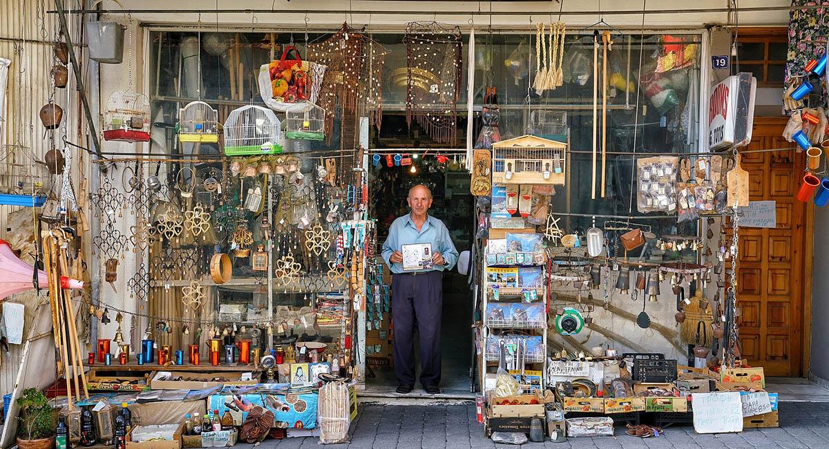 Old man standing in door of junk shop