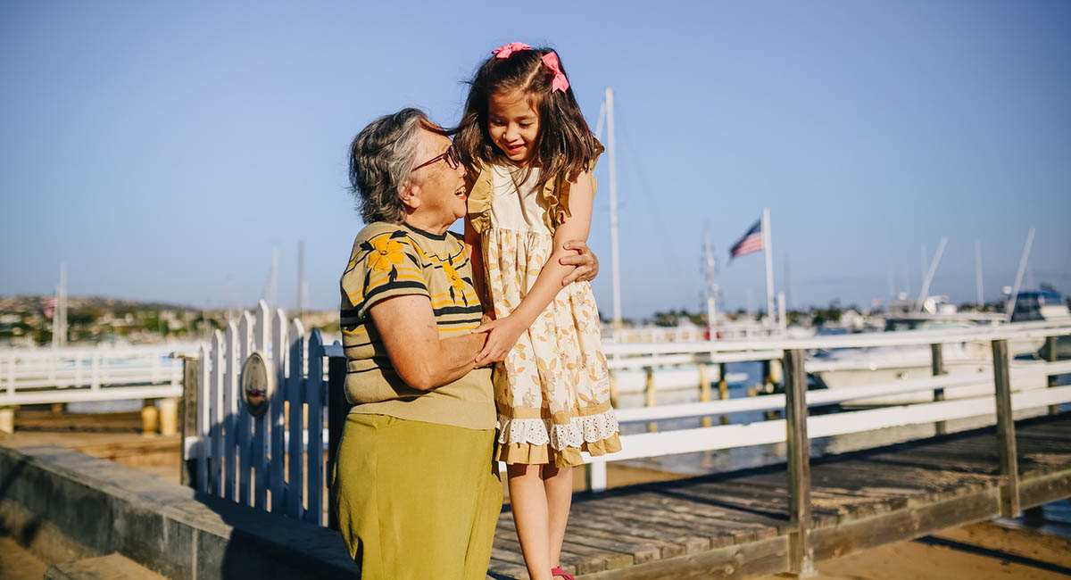 Older woman holding young girl who's standing on a low wall