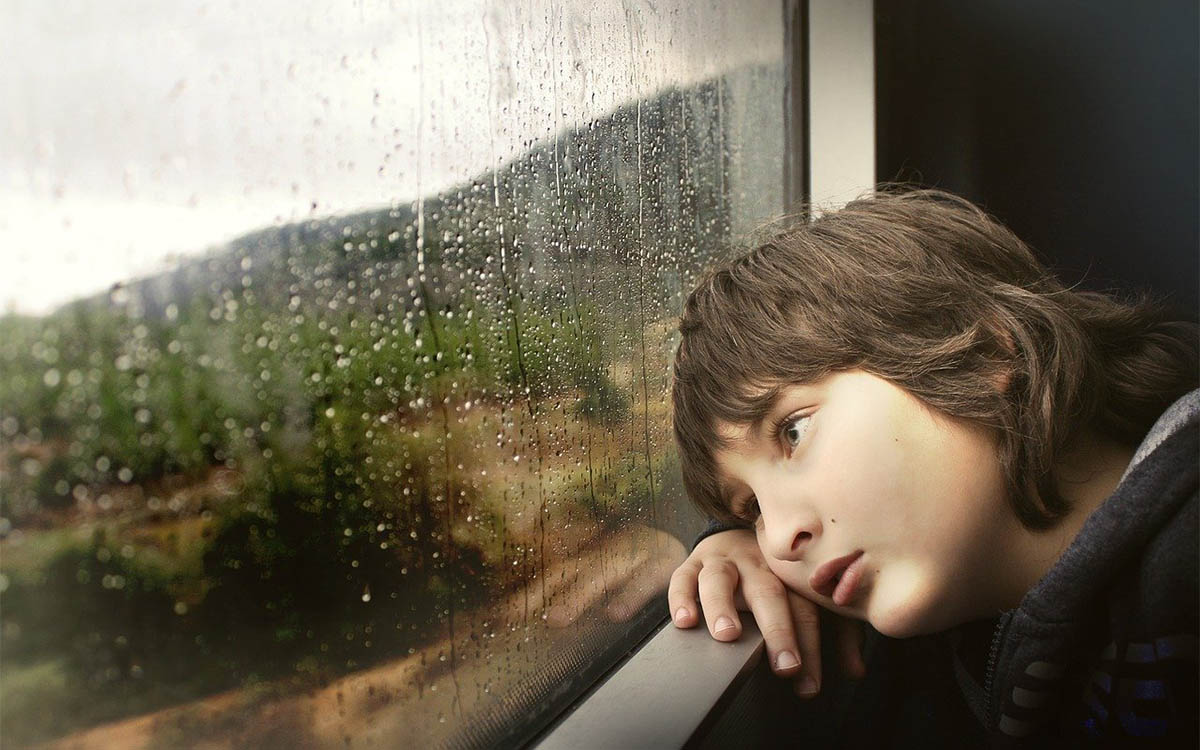child looking out train window in the rain with a sad expression