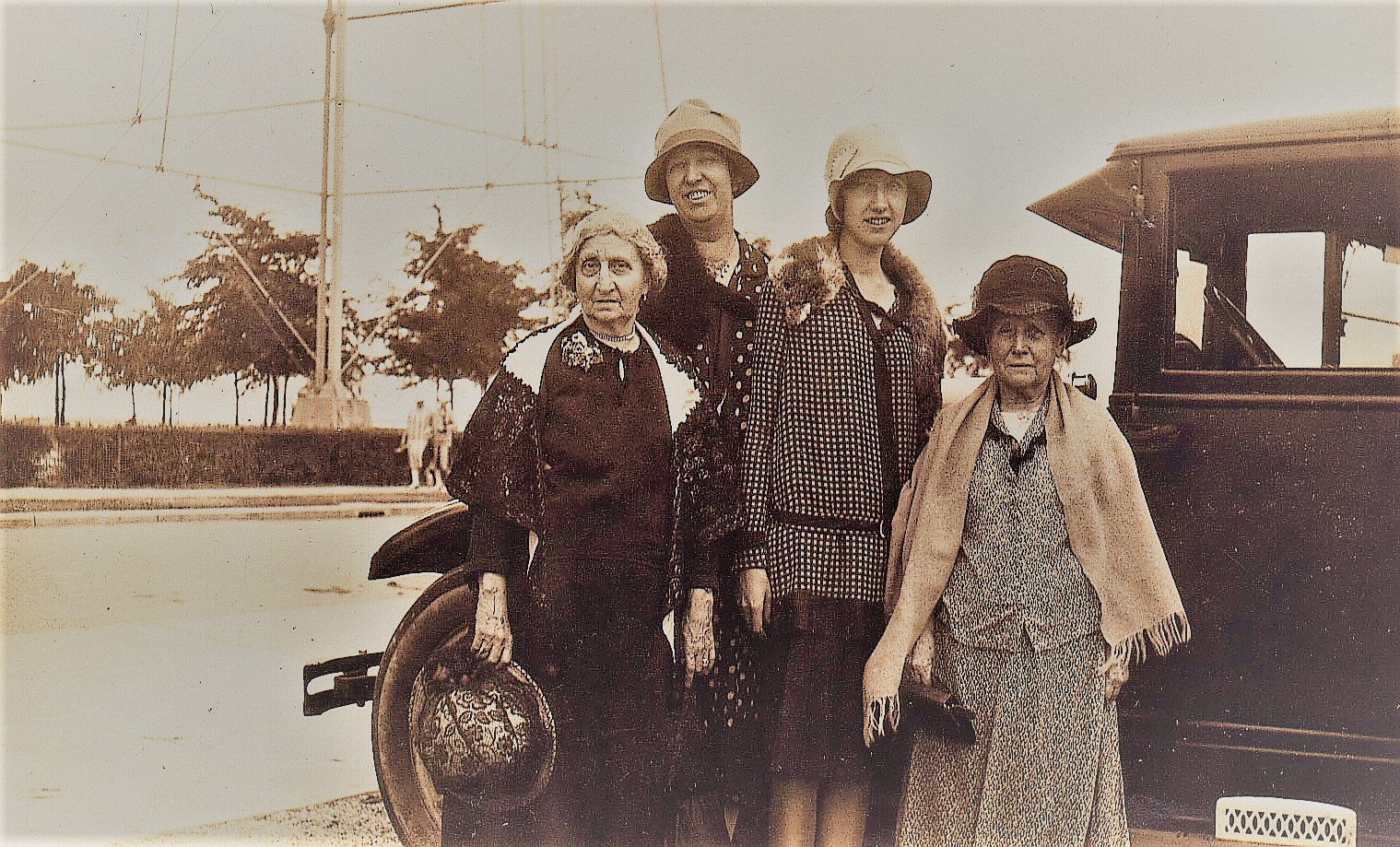 Four women standing by an automobile  in the 1920s