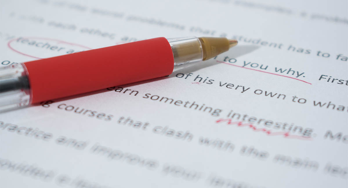 Red pen lying on paper with corrections to text