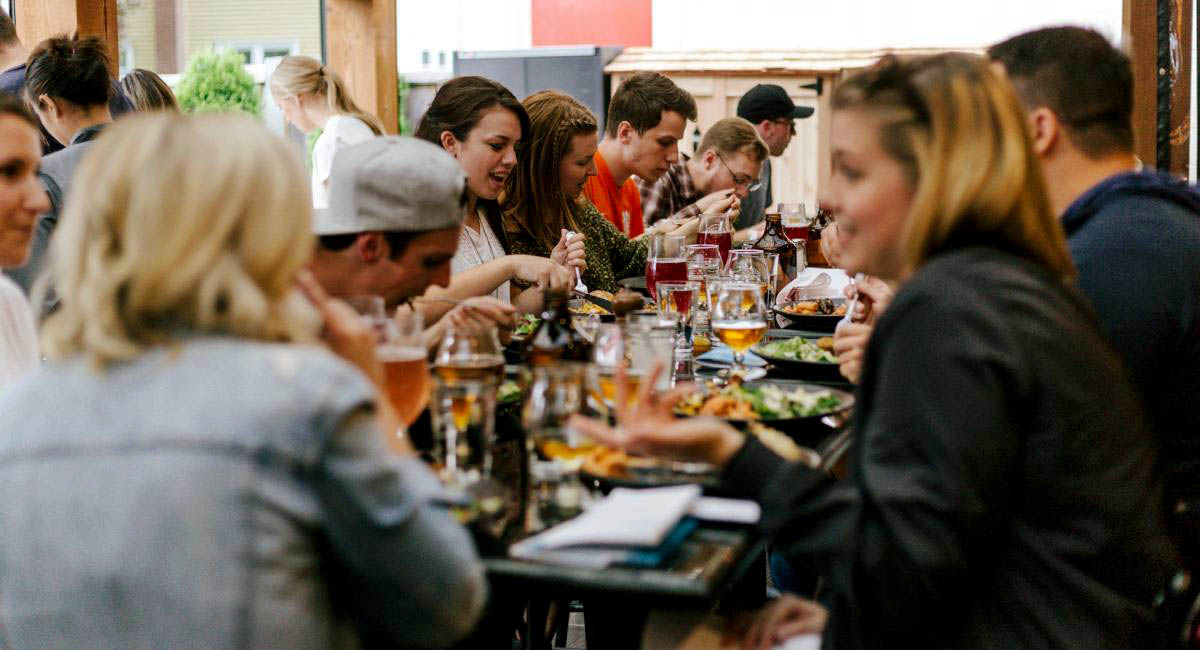 People eating at a long table in a restaurant