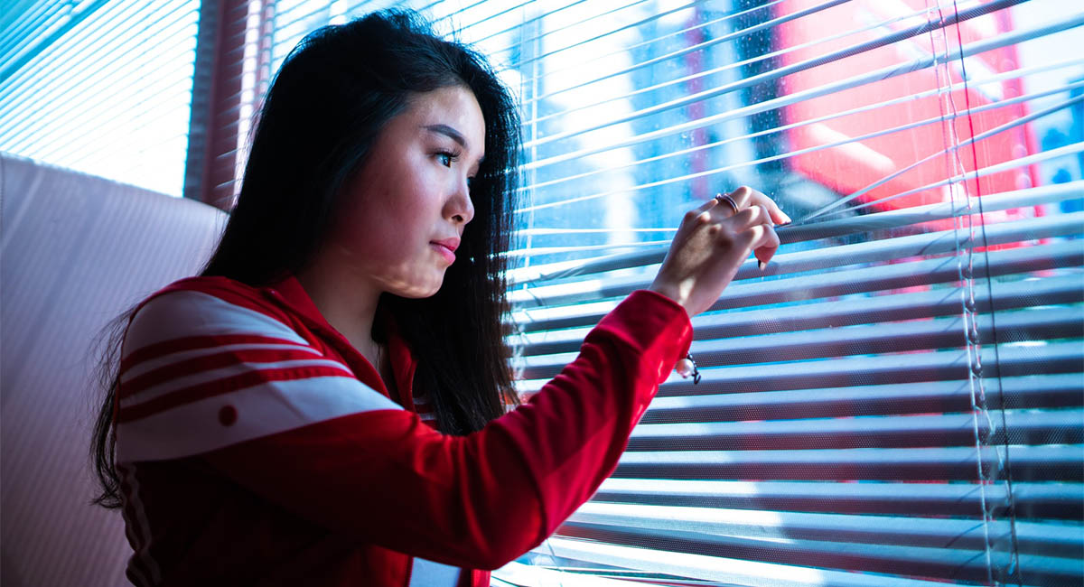 Young woman looking out a window through venetian blinds