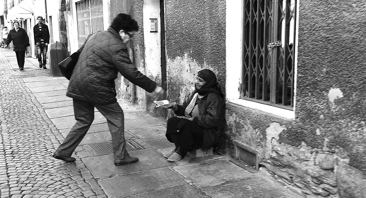 Man giving money to a beggar on the street