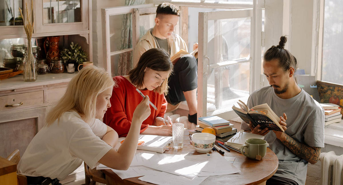 Four young people sitting at a table in an apartment doing different things