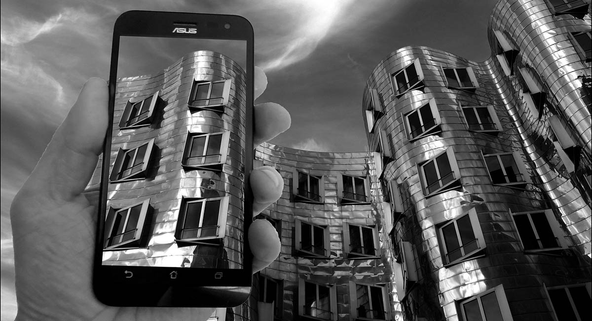 monochrome mobile phone screen with architecture also seen behind it