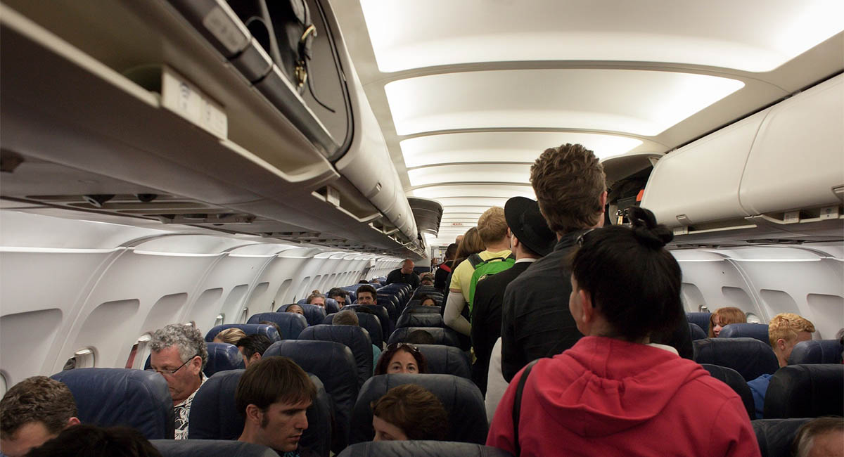 Passengers boarding crowded airplane