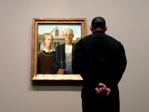 "Man looking at Grant Wood's ""American Gothic"" painting"