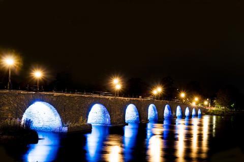Long stone bridge over water at night