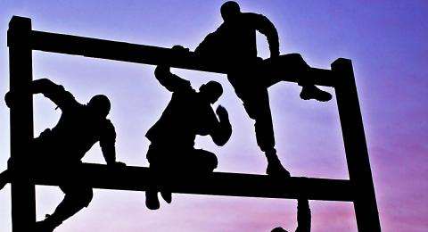 Silhouette of men climbing rails in obstacle course
