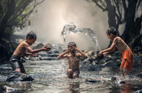Three boys playing in a river, splashing each other