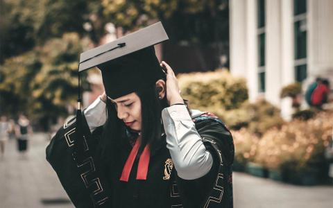 Young woman wearing graduation gown and mortar board