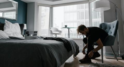 Young man in bedroom putting on his shoes