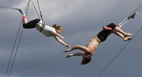 Woman learning trapeze with man catching her