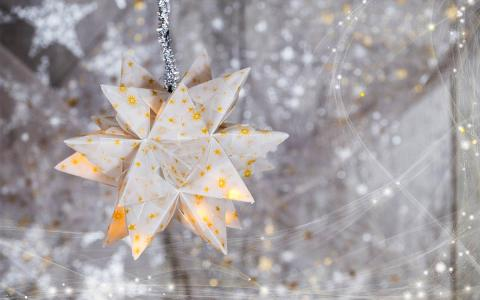 Paper star hanging in front of blurred strings of lights