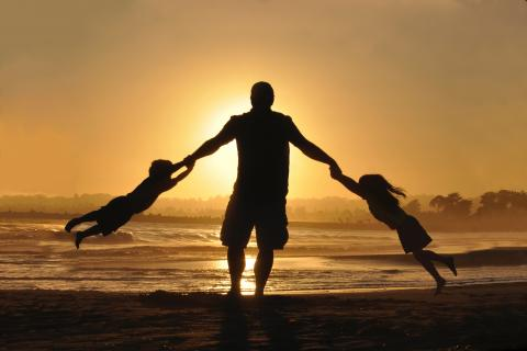 Silhouette of a man swinging two children by the hands on a beach