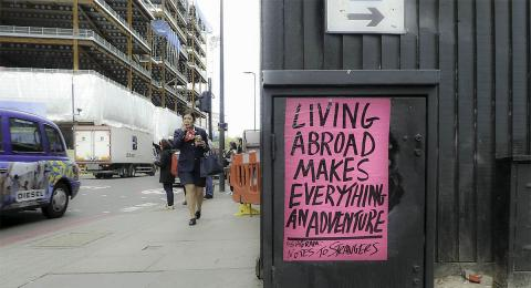 """Sign on metal box along the street that says """"Living abroad makes everything an adventure"""""""