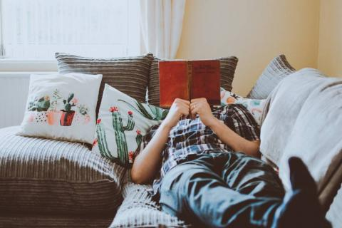 Person lying on a couch with a book in front of their face