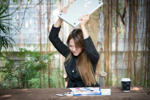 Woman throwing laptop in frustration