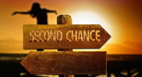 """arrow sign """"second chance"""" with woman in background, brown on orange"""