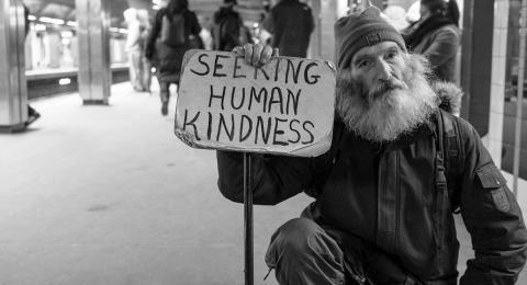 "Homeless man holding sign ""Seeking human kindness"""