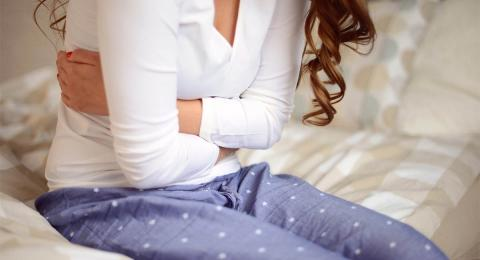 torso of a woman on a bed holding her stomach
